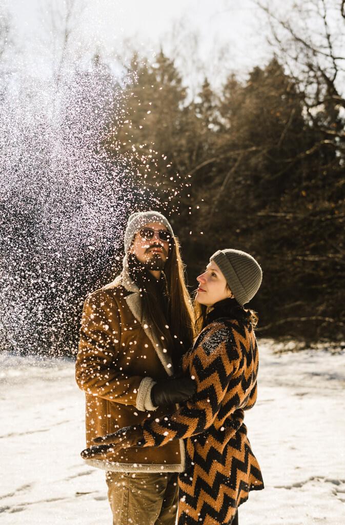 Paar steht in winterlicher Kleidung im Schnee und es rieselt Schneeflocken.