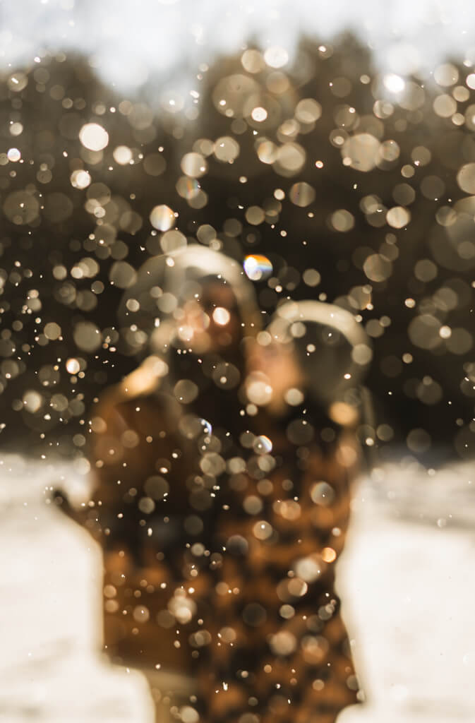 Paar steht verschwommen im Hintergrund von Schneeflocken verdeckt.