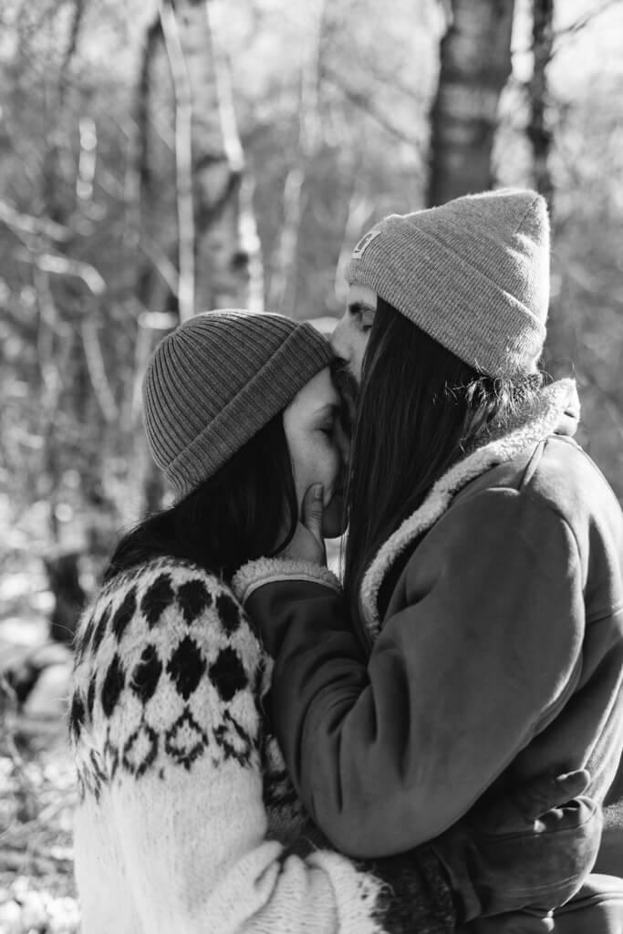Schwarz weiß Aufnahme Mann küsst seine Frau auf die Stirn.