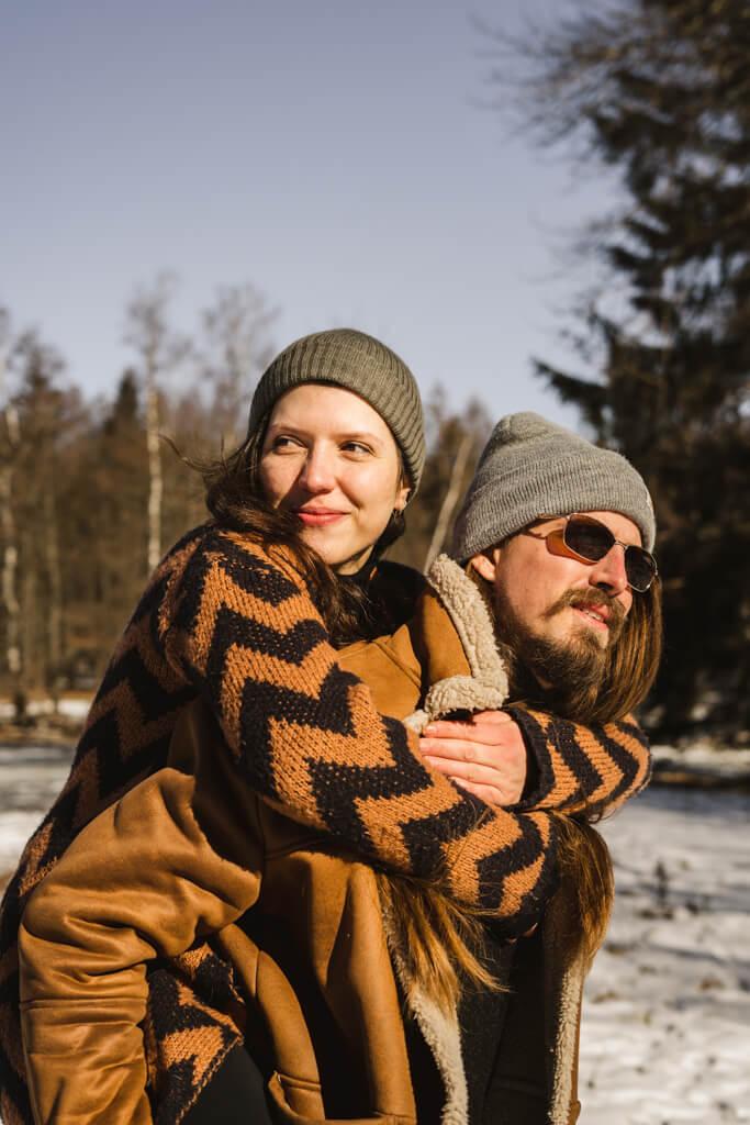 Paarshooting Frankfurt im Schnee trägt der Mann seine Frau Huckepack.