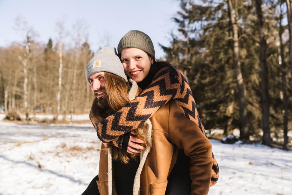 Mann trägt seine lachende Frau huckepack durch den Schnee.