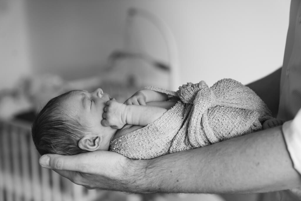 Papa hält sein Neugeborenes auf den Unterarmen.