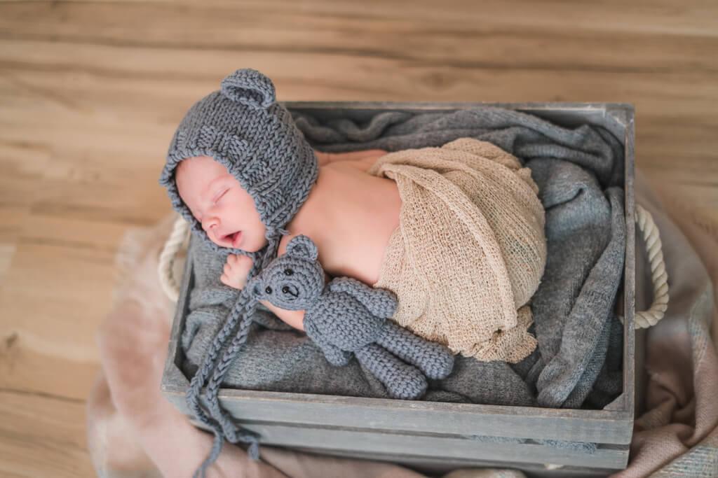 bei der Babyfotografie in Frankfurt liegt in einer grauen Kiste während des Neugeborenenshootings mit einer Bärchenmütze auf.