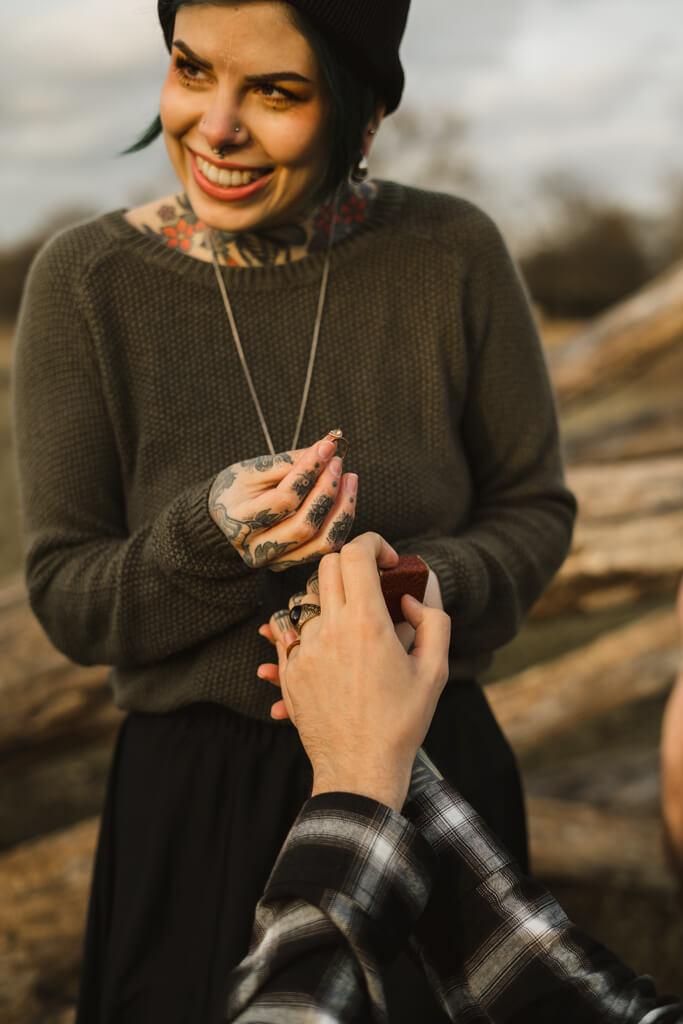 Frau nimmt ihren Verlobungsring entgegen und lacht.