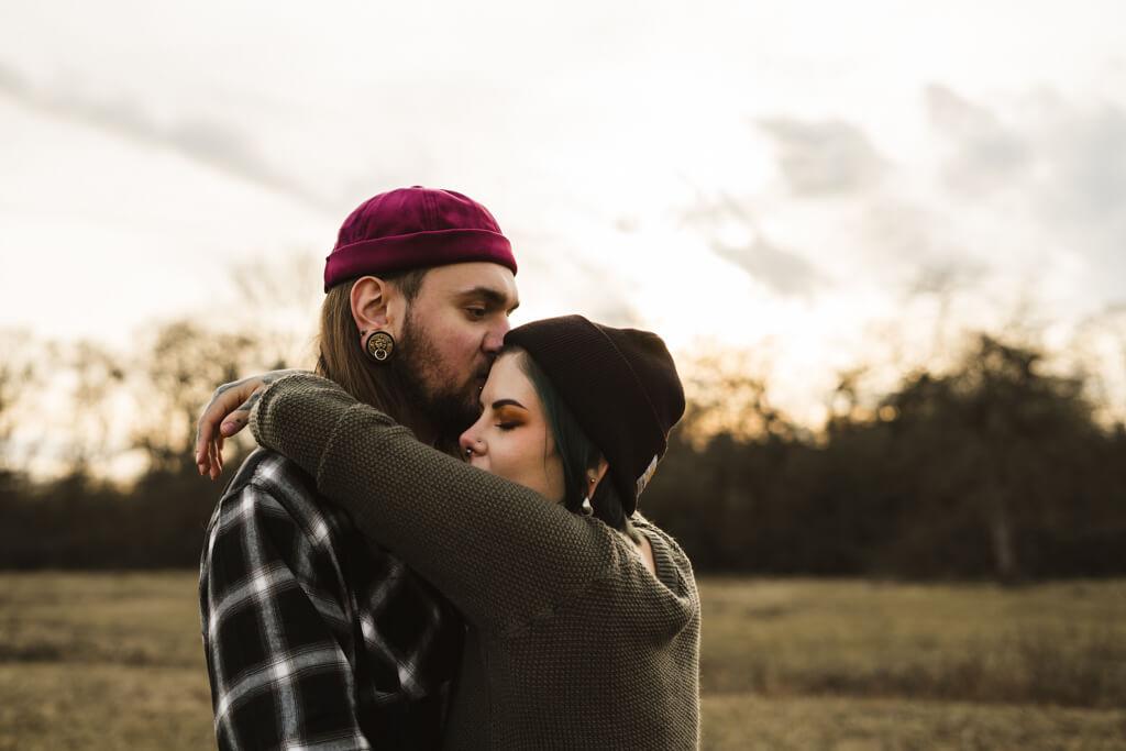 Paar auf einer Wiese beim Sonnuntergang und hält sich eng in den Armen.
