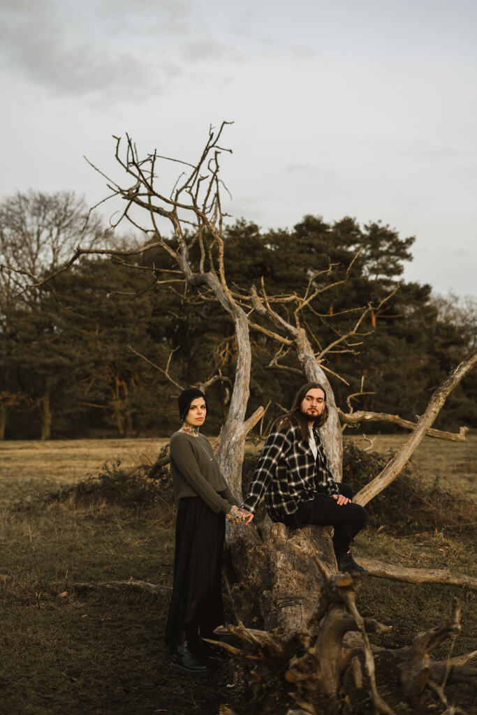 Tätowiertes Pärchen sitzt auf einem Baumstamm und poste in die Kamera während eines Paarshootings.