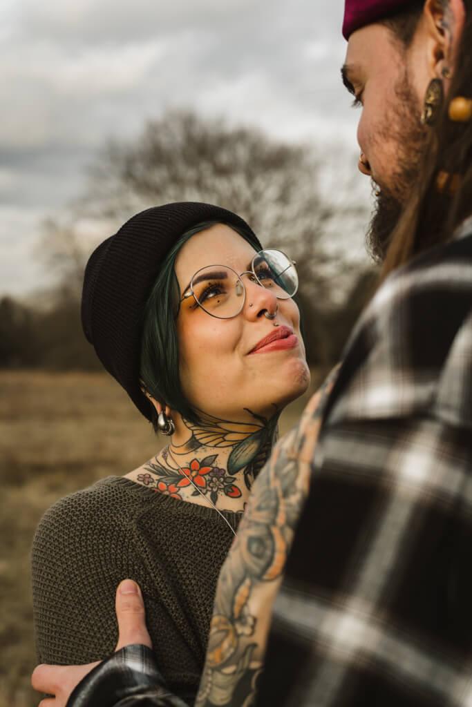 Tätowierte Frau mit Brille schaut verliebt in die Augen ihres Verlobten.