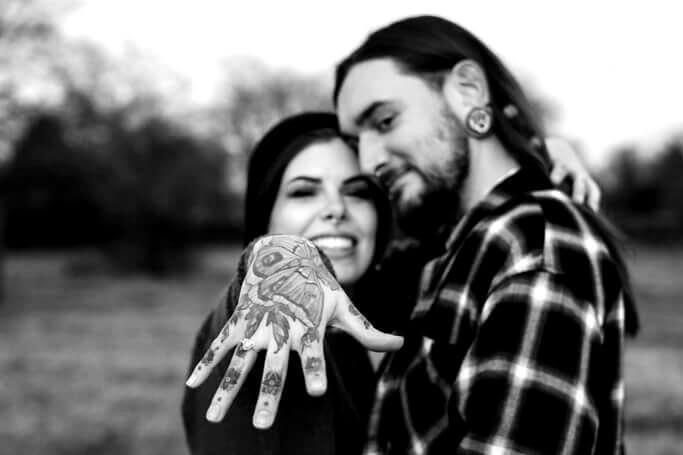 Nach dem Hochzeitsantrag hält die Frau ihre Hand mit dem Verlobungsring in die Kamera.