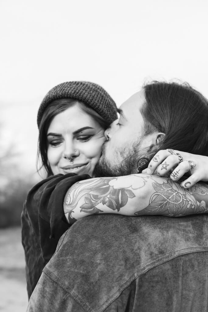 Mann halt seine Frau nach dem Hochzeitsantrag in den Armen und küsst sie auf die Backe.