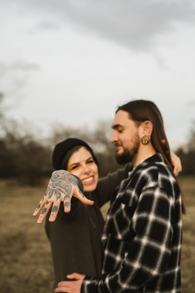 Frau streckt ihre tätowierte Hand mit dem Verlobungsring in die Kamera.
