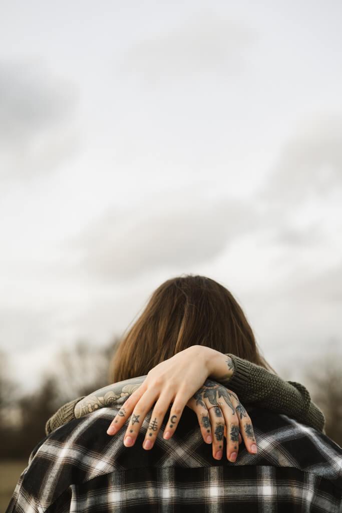 Frau mit tätowierten Händen über den Schultern ihres Mannes mit ihrem Verlobungsring.