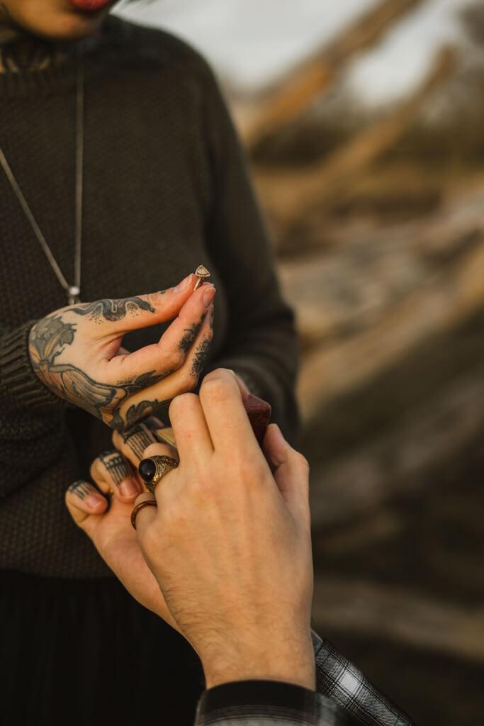 Tätowierte Frau hält ihren Verlobungsring in der Hand.