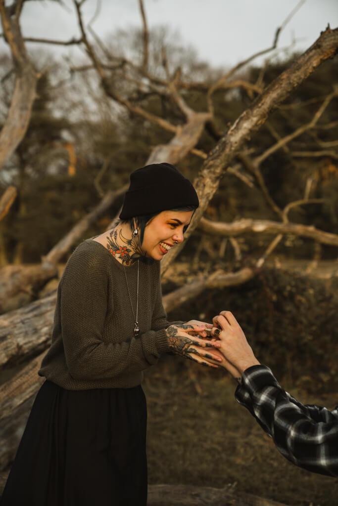 Tätowierte Frau freut sich über ihren Hochzeitsantrag und hält den Verlobungsring in der Hand.
