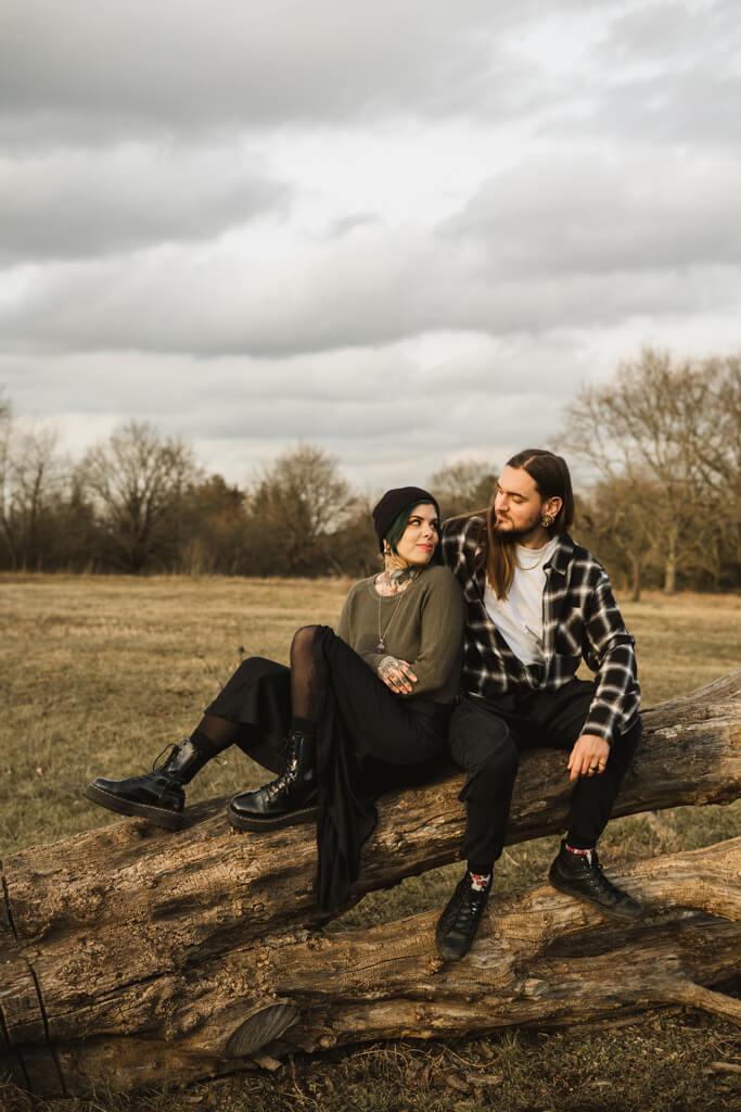 Paar sitzt auf einem Baumstamm und kuschelt.