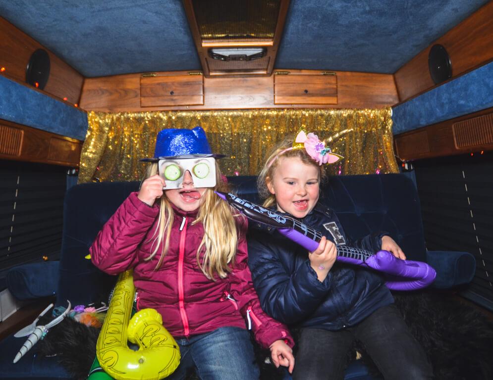 Zwei Kinder im Fotobus verkleidet und Posen für die Photobooth Kamera.