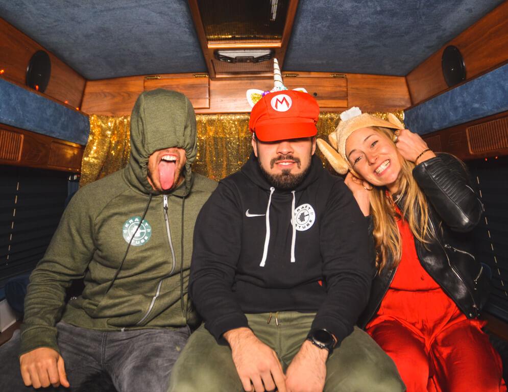 Drei Freunde sitzen im Fotobus und machen verkleidet ein Foto zusammen.