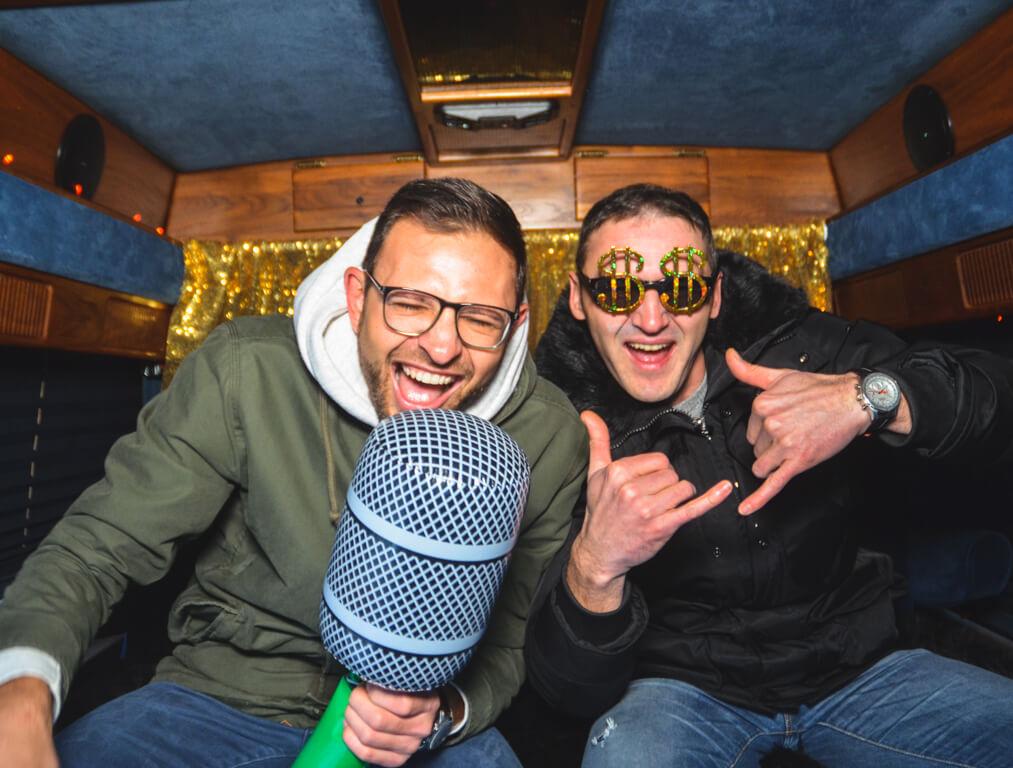 Zwei Männer sitzen im Fotobus Big Eddie und machen ein Selfie mit riesen Mikrofon.